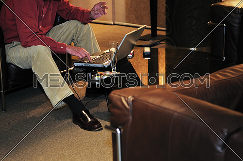older senior businessman woking on laptop at hotel lobby