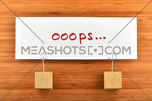 Oops, looks we have problem, one big white paper note with two wooden holders on wooden bamboo background for presentation