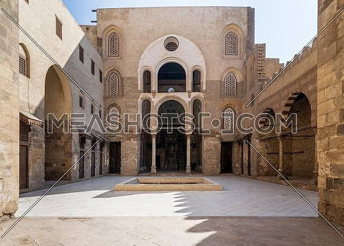 Main Iwan at courtyard of public historic mosque of Sultan Qalawun with huge arches, wooden doors and decorated windows, Cairo, Egypt