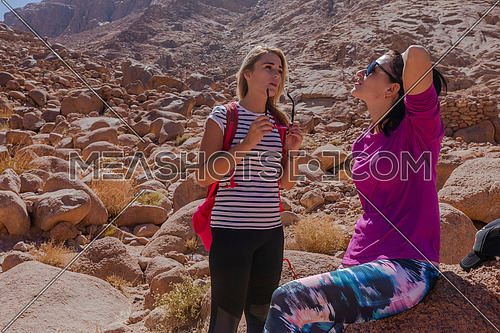 Long shot for two female tourists exploring the Sinai Mountain at wadi Freij by day.
