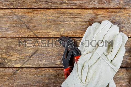 Building protective gloves with adjustable wrench on old wood background