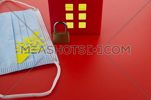 Epidemic, social isolation, coronavirus COVID-19 concept with brass padlock, medical face mask and red house with light shining through the windows and free copy space for text