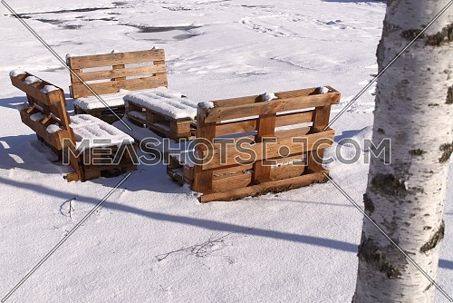 Snowy outdoor furniture made from wood pallets in winter near birches
