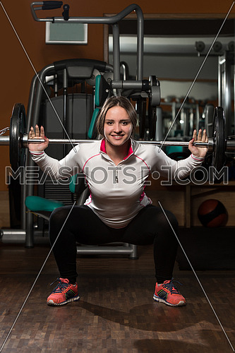 Young Woman Performing Barbell Squats - One Of The Best Body Building Exercise For Legs
