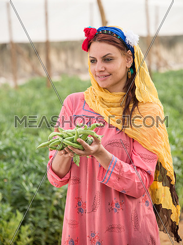 A female farmer holding raw broad beans in the palm of her hands