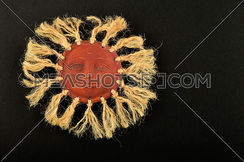 Mexican traditional ceramic happy sun face symbol plate with rays of jute rope isolated on black