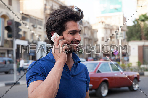 A young man in the street talking on his mobile