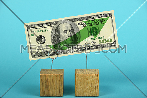 Growth and support of American economy and US dollar, one dollar banknote with green arrow up on two holders over blue background