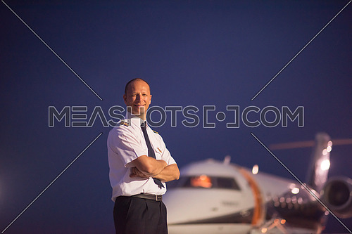 Portrait of a young middle eastern successful pilot in front of private jet one summer evening