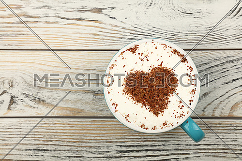 Close up blue cup full of latte cappuccino coffee with heart shaped chocolate on milk froth over background of white vintage wooden planks table, close up, elevated top view, directly above