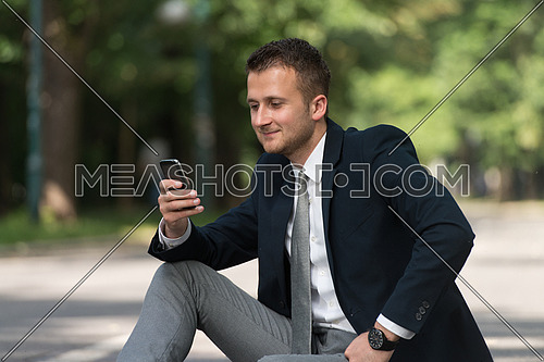 Happy Business Man Using Mobile Phone Outside Sitting On Asphalt