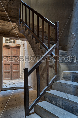 Ascending staircase with wooden balustrade and wooden closed ornate door at the background, Prince Taz palace, old Cairo, Egypt