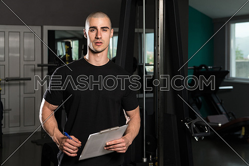 Portrait Of A Personal Trainer In The Gym With Clipboards In His Hands