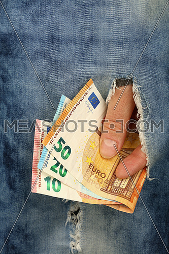 Hand holds several different value Euro paper currency banknotes in jeans rip hole, low angle view