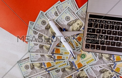 Cash in american dollar banknotes with plastic airplane model and laptop computer keyboard