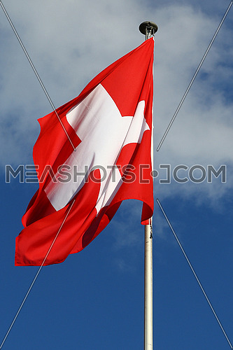 Flag of the Federal State of Switzerland flapping in the wind against blue skies and white clouds