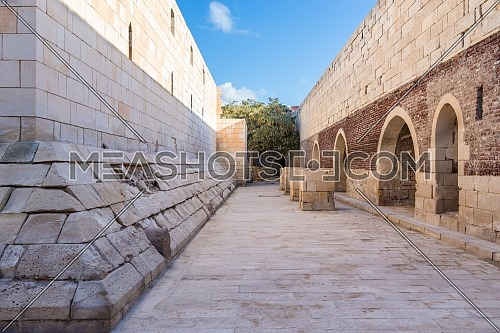Exterior of ancient passage with shabby red bricks passage and crumbling arched alcoves on street, Citadel of Qaitbay, Rashid, Egypt