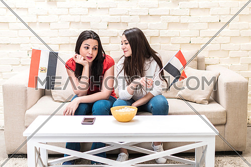 two young ladies sitting on a sofa in front of white table with a mobile phone on and bowl of popcorn, holding two small egyptian flags