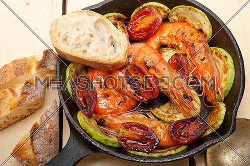 roasted shrimps on cast iron skillet  with zucchini and tomatoes