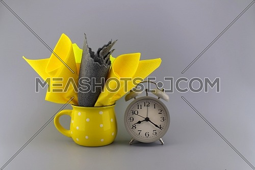 Yellow and gray napkins placed in the yellow cup next to the gray vintage alarm clock on gray background with space for text