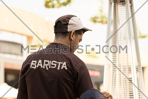 A barista dressed in brown uniform serving hot coffee in an outdoor area of a coffeshop