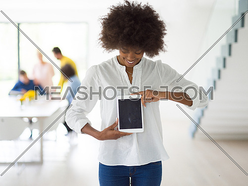 african american Businesswoman using tablet with coworkers in backgorund having meeting
