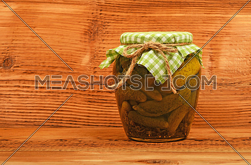 One glass jar of homemade pickled cucumbers with green checkered textile top decoration at brown painted vintage wooden surface