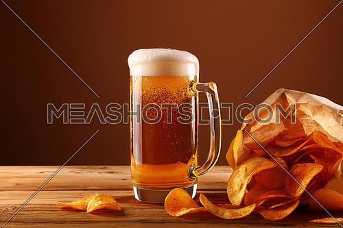 Close up one glass mug of lager beer with white froth and bubbles and paper bag of potato chips on wooden table over dark brown background with copy space, low angle side view