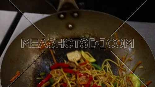 Close up cooking stir fried noodles with meat and vegetables, carrots, pepper and zucchini, in wok pan on open gas fire, high angle view
