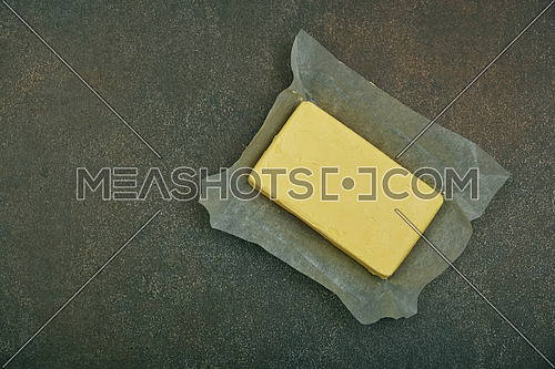 Close up open fresh yellow hard stick butter in paper on grunge table surface, elevated top view, directly above