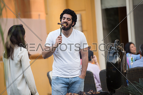 Young middle eastern couple preparing a barbecue for friends summer evening and enjoy it