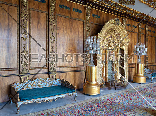 Manial Palace of Prince Mohammed Ali Tawfik. Residence of prince's mother with golden ornate niche, blue couch and ornate wooden wall, Cairo, Egypt