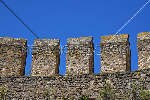 Medieval fortress or castle vallum, defensive stone wall over background of clear blue sky