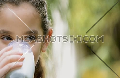 a cute little middle eastern girl drinking a glass of milk health concept