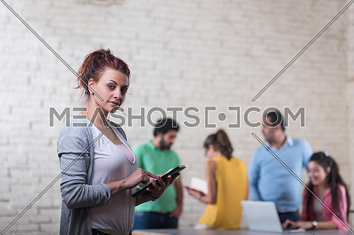 young middle eastern informal business woman enjoys in the creative office using tablet computer