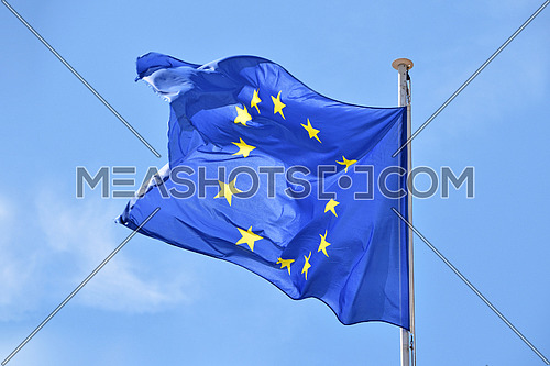 Close up flag of EU, European Union waving and blowing in the wind over blue sky, low angle view