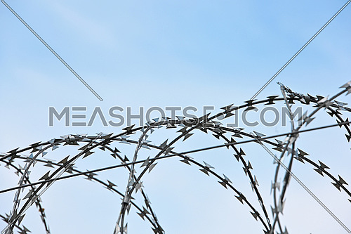 Close up barbwire security rolls protection over blue sky background with copy space, low angle side view
