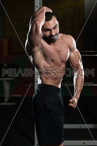Young Man Standing Strong In The Gym And Flexing Muscles - Muscular Athletic Bodybuilder Fitness Model Posing Showing Abs After Exercises