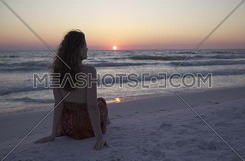 A woman relaxing by the beach at sunset