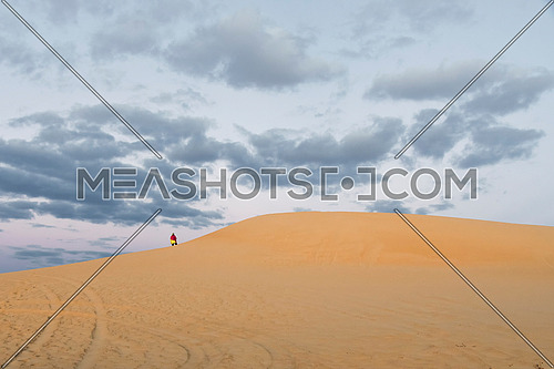 Girl with colorful wear standing on top of high sand dunes with cloudy blue sky background in Siwa Oasis, Egypt Adventure and Tourism wallpaper.