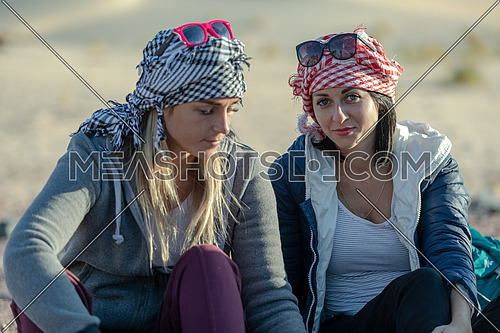 mid shot for two female tourists wearing bedouin traditions headscarf at Ain hodouda in Sinai at day