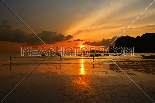Sunset sea beach during low tide with long tail boat silhouettes and reflection of vivid sky