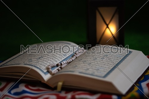 Close up shot for Holly Quran Book open with Misbaha inside showing Ramadan Lantern in the background.