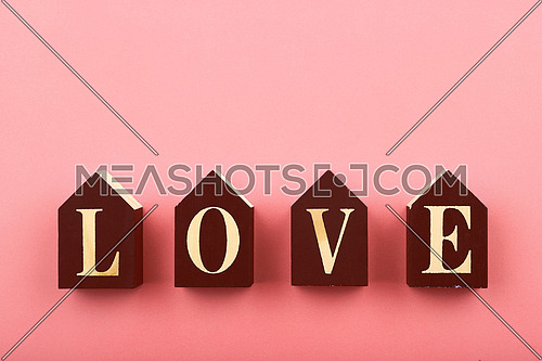 Wooden house shaped cube signs with LOVE word over pastel pink background and copy space, low angle view