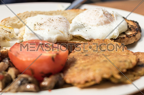 Two poached eggs on toast and tomato on the side