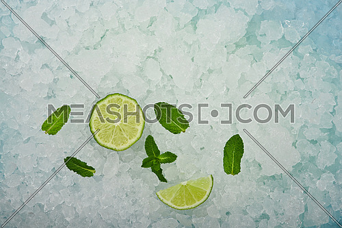 Close up fresh juicy green lime cut half and wedge slice and mint leaves over background of crushed ice, elevated high angle view, directly above