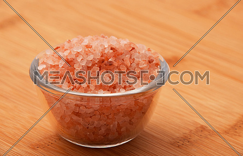 Himalayan pink salt in tiny transparent glass bowl on wooden bamboo background