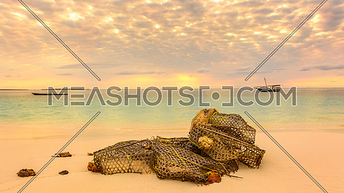 In the beautiful beach of Nungwi (Zanzibar) in the forground a fishing net on the beach,in background two typical local boats (dhows) at sunset.