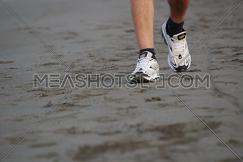 A close shot on sports shoes on the beach