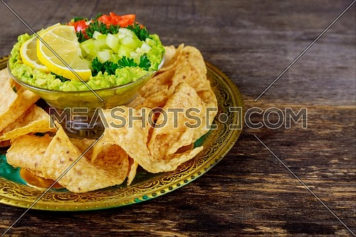 Guacamole with tortilla chips in fresh ingredients over vintage rusty a bowl on a dark wood background. Top view with copy space.